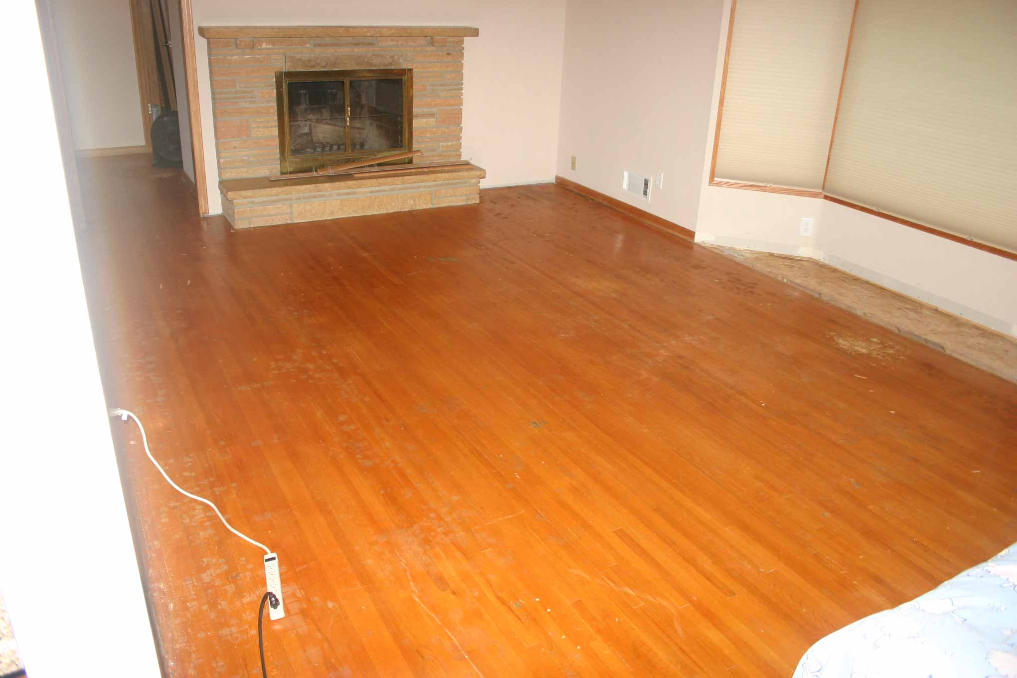 Before photo of hardwood flooring in living room