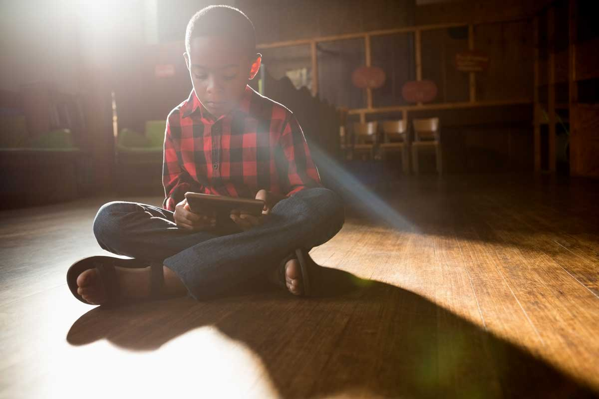 Boy Sitting On Wooden Floor In The Sun