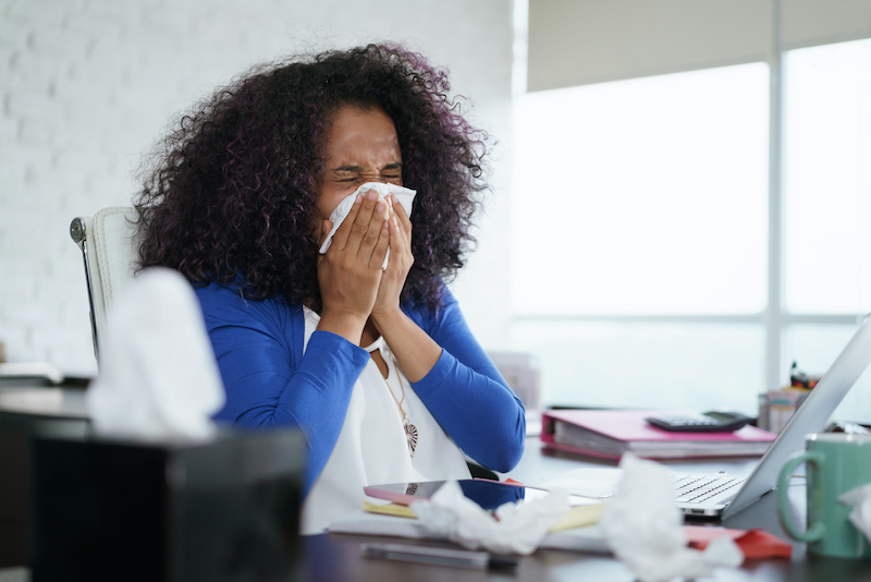 Woman Sneezing in Home Office