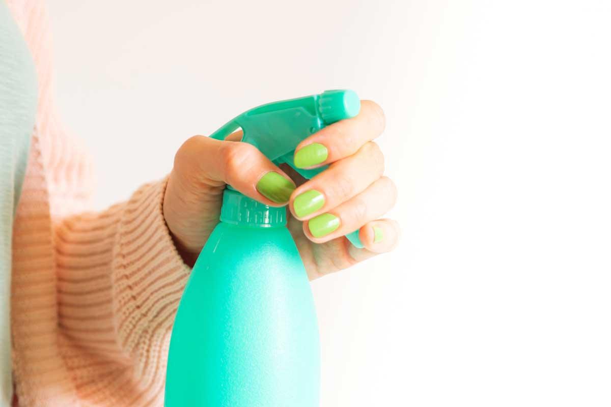 Womans Hand Holding Mint Green Spray Bottle Gj677xt